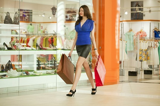 Beautiful young woman in black skirt, holding shopping bags walking in the shop