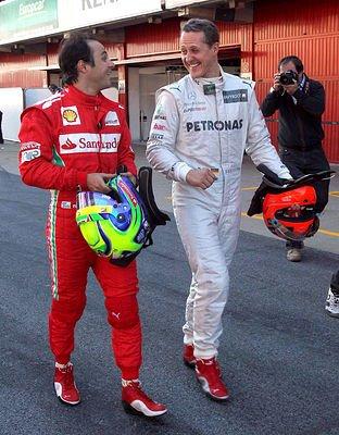 Фелипе Масса и Михаэль Шумахер идут и смеются по пит-лейну на предсезонных тестах 2012 в Барселоне 23 февраля 2012