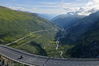 Furkapass, Westrampe. Blick ins Rhonetal.  Links die Furkastraße, die im Rhonetal in Richtung Mont Blanc nach Frankreich führt. Unten am Talausgang das Örchen Gletsch, wo die Grimselstraße abzweigt und sich hinauf zum Grimselpaß windet.