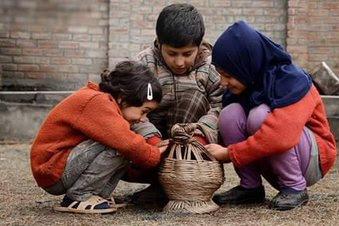 Kashmiri children warming their hands amid chilly weather in Kashmir