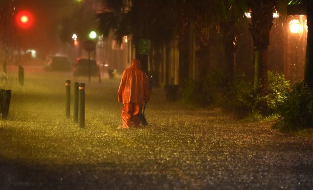A communal worker walks at a flooded street in downtown Charleston, SC on 3 October 2015. Much of the US southeast was under water Saturday, deluged by rains from Hurricane Joaquin, with forecasters predicting more historic flooding in coming days for the already waterlogged region. Photo: AFP / Getty Images