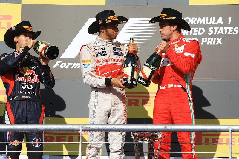 Себастьян Феттель и выпивающее без него Льюис Хэмилтон и Фернандо Алонсо на подиуме Гран-при США 2012