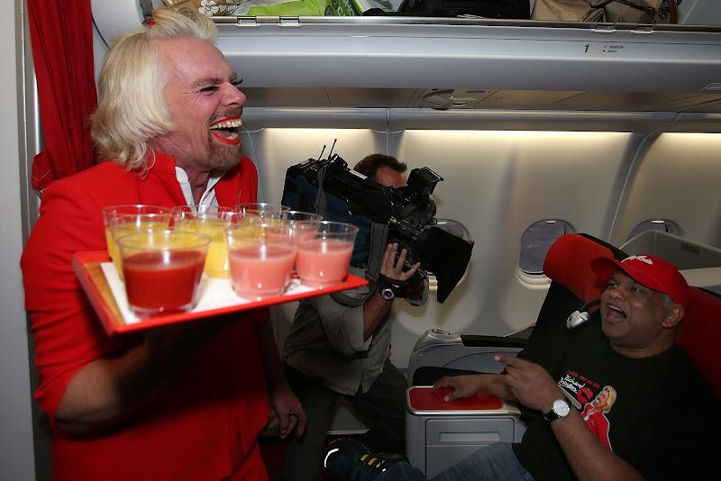 Сэр Ричард Брэнсон в роли стюардессы на борту самолета AirAsia Тони Фернандеса 12 мая 2013