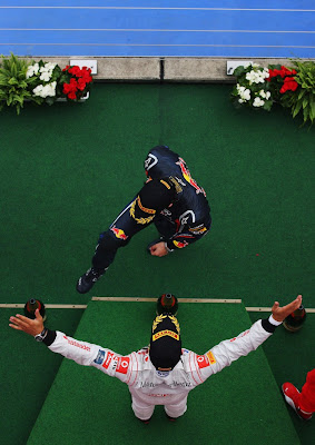 Льюис Хэмилтон раскрывает свои объятия перед Марком Уэббером на подиуме Гран-при Германии 2011