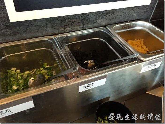 台南南港-飯樂丼。等待取餐前可以先把鰹魚高湯裝好,並把這三種配菜(蔥花、海帶芽、天婦羅酥)都給加到高湯中,當然還可以先把芥末、佐料弄好找個餐桌先佔位置。