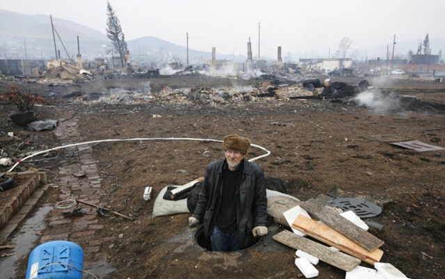 A man kneels amidst the burned remnants of his home after wildfires struck the Khakassia region of Siberia on 13 April 2015. Photo: Ilya Naymushin / Reuters