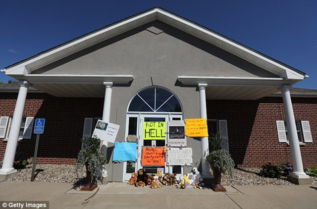 Closed for business: Dr. Walter Palmer's dental practice abruptly closed on Tuesday morning, 28 July 2015. Signs outside the office read, 'Rot in hell' and 'There's a deep cavity waiting for you!' Photo: Getty Images