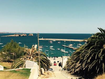 Utsikt ned en trapp mot en havn med små båter.