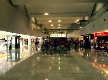 Bilde av en hall med butikker på begge sider.