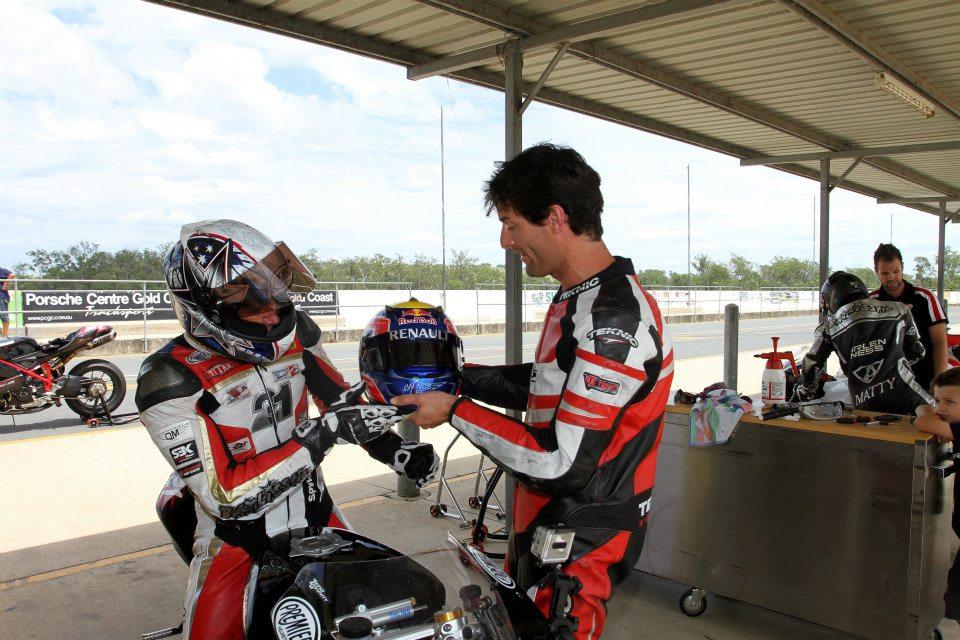 Марк Уэббер показывает свой шлем Трою Бэйлиссу на Queensland Raceway 29 декабря 2011