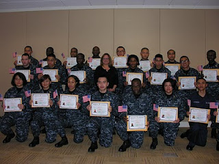 USCIS Chicago District Director Ruth Dorochoff stands with a group of newly naturalized Navy recruits