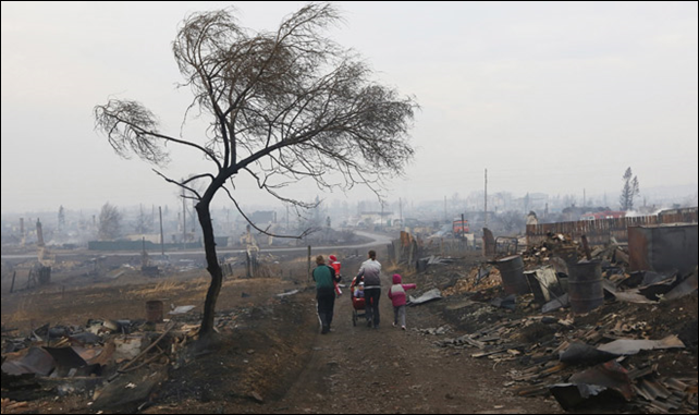 Family members walk away while passing the debris of destroyed buildings in the settlement of Shyra, damaged by recent wildfires, in Khakasia region, 13 April 2015. Photo: Ilya Naymushin / Reuters