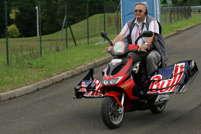 маршал едет на мопеде с передним крылом Red Bull Марка Уэббера на Гран-при Венгрии 2011