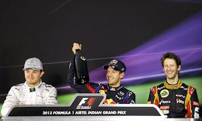 Себастьян Феттель с бутылкой шампанского и Нико Росберг и Ромэн Грожан на пресс-конференции после гонки на Гран-при Индии 2013