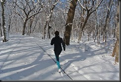 Cheryl runs down the trail.   The trees keep the snow limited.