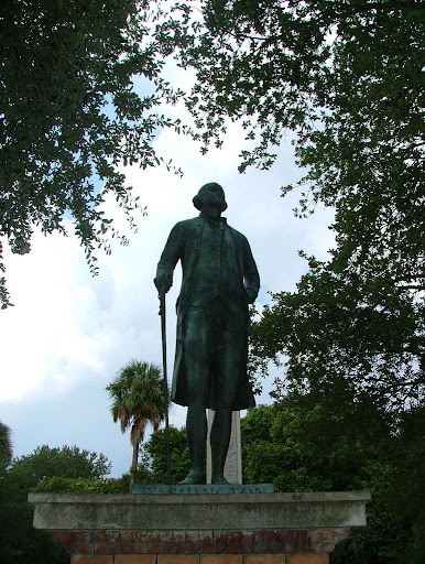 A statue of George Washington stands in a small park in the middle of Charleston