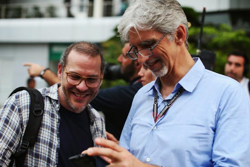Деймон Хилл показывает что-то на телефоне Жаку Вильневу на Гран-при Малайзии 2014