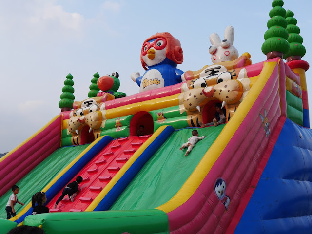 children playing on a large inflated Pororo-themed slide at Donghu Park in Zhuzhou, Hunan
