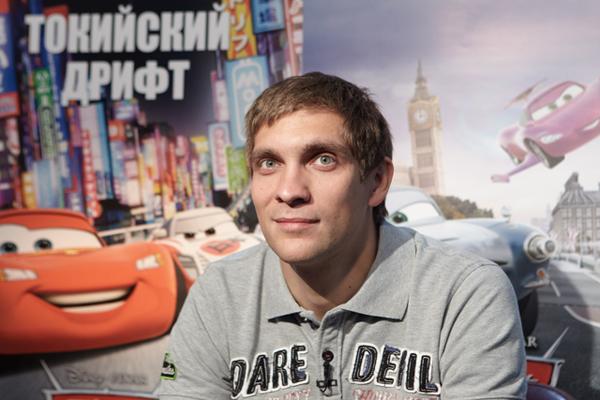 Виталий Петров на фоне плаката Тачки 2