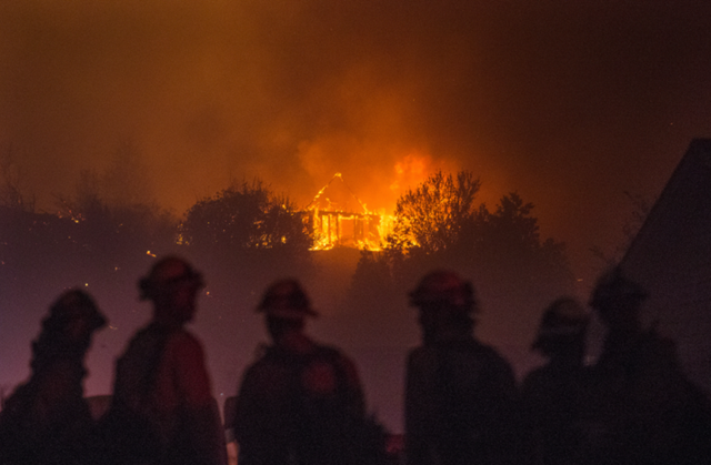 Forest Service fire fighters from Leavenworth watch as a house burns in northern Wenatchee on 28 June 2015. Photo: Don Seabrook / The Wenatchee World