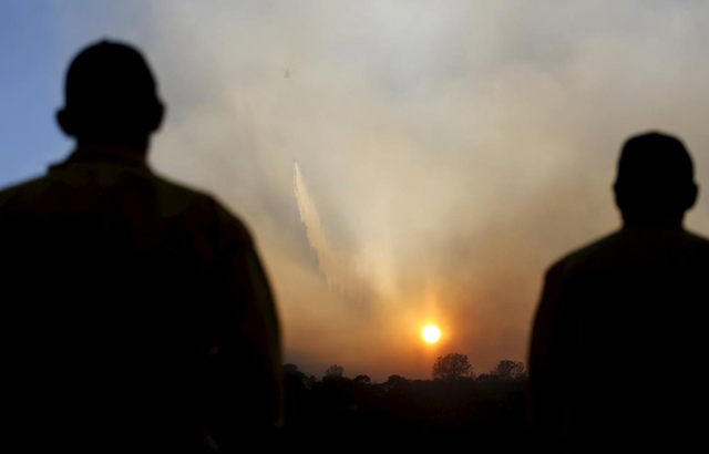 Firefighters look on as a helicopter drops water on the Wagg Fire near Lake Berryessa, California, on 23 July 2015. A rapidly expanding wildfire in Northern California is threatening about 150 structures and has forced evacuations in several rural areas as the wind-whipped blaze rips across parched vegetation, officials said on Wednesday. Photo: Robert Galbraith / REUTERS