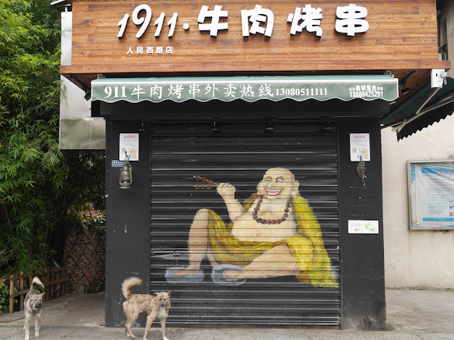 two dogs in front of a Chinese barbecue shop