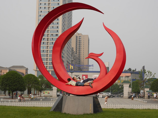two boys lying on a large circular red sculpture