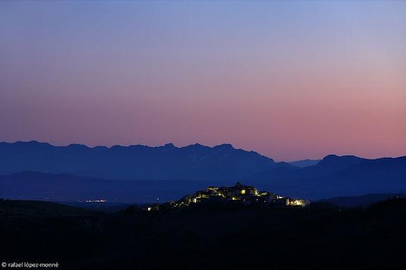 El poble de Gratallops al capvespre, vista des de Torroja, DOQ Priorat, al darrera, les llums de Mora d'Ebre (Ribera d'Ebre) i al fons el massís dels Ports (Terra Alta)Priorat, Tarragona