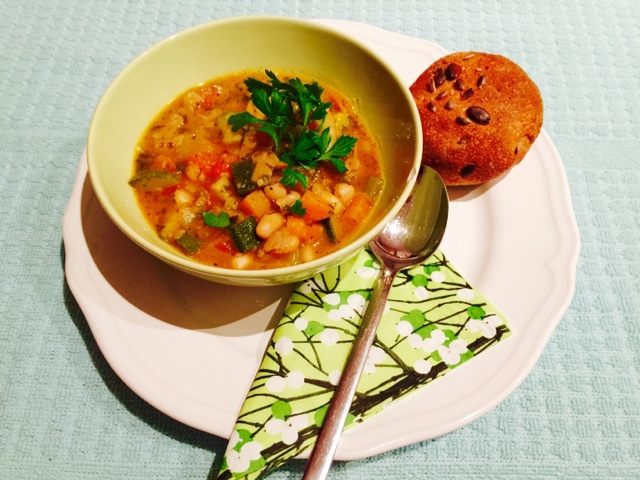 A bowl of classic Italian minestrone soup with a seeded wholemeal bun
