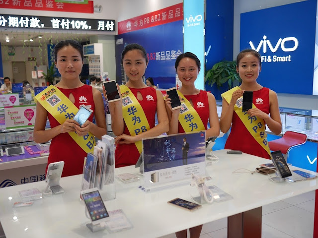 four young women promoting Huawei mobile phones inside a store in Changsha