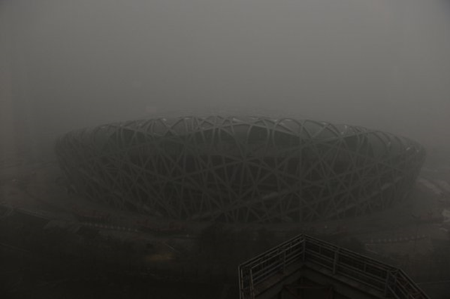 Beijing's National Stadium, also known as the Bird's Nest, is barely visible through the dense smog that triggered the city's first pollution red alert, 7 December 2015. Photo: Xinhua News / Twitter