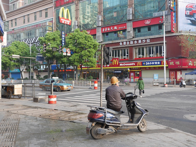 motorbike taxi driver waiting at an intersection in Hengyang, Hunan