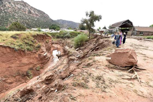 Residents of Hildale, followers of Warren Jeffs, Utah look down an estimated 50-foot-deep gorge that was created after a '100-year' flash flood, 15 September 2015. Photo: David Becker / Reuters