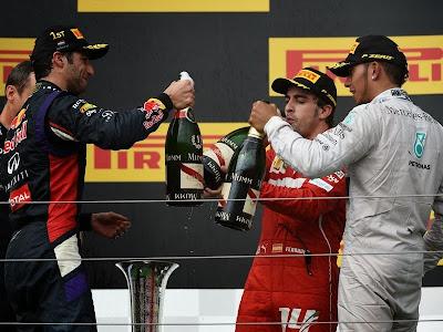 Даниэль Риккардо, Фернандо Алонсо и Льюис Хэмилтон чокаются шампанским на подиуме Гран-при Венгрии 2014