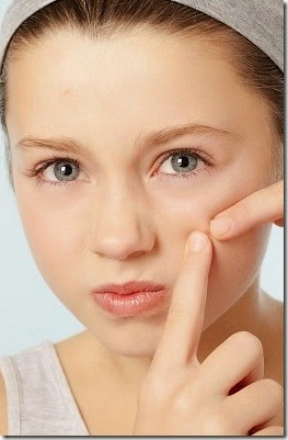 girl picking at her pimple