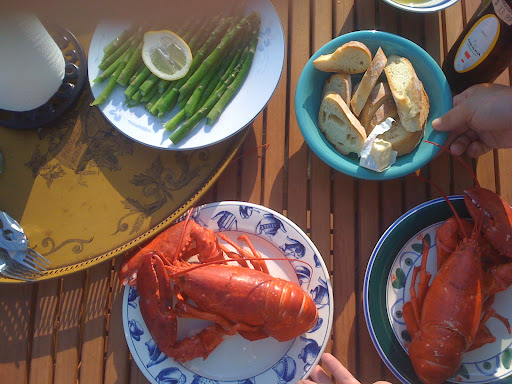 Steamed lobsters, asparagus with lemon, and fresh bread.