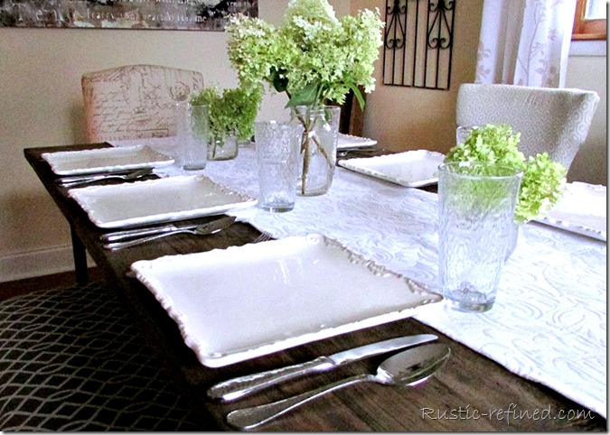 Summer Tablescape Idea using white dishes, an elegant flower arrangement on a farmhouse dining table