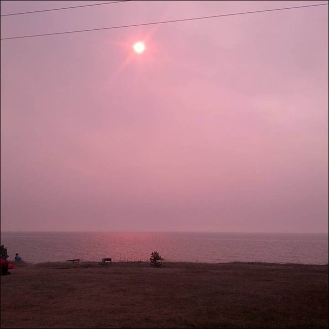 The sun appears pink as smoke rises from forest fires around Lake Baikal, Siberia, on 10 August 2015. Photo: Vladimir Borovikov / The Siberian Times