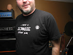 """Steve's T-Shirt is a cipher.  Rearrange the letters and you get the Organical Credo:    """"Mechanize Above Papalise""""       Oh yes, the machine rules all."""