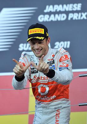 Дженсон Баттон показывает победный символ на подиуме Гран-при Японии 2011