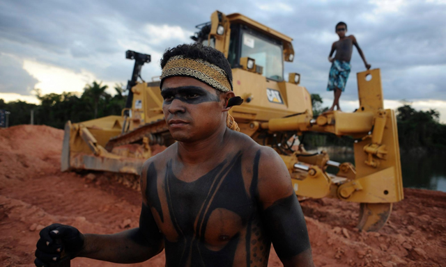 Two Amazon Indians stand near a heavy machinery being used in the construction of the massive Belo Monte hydroelectric dam during a 2012 protest. Photo: Reuters