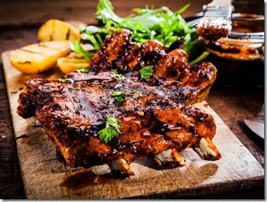 27054584-delicious-barbecued-ribs-seasoned-with-a-spicy-basting-sauce-and-served-with-chopped-fresh-herbs-on-