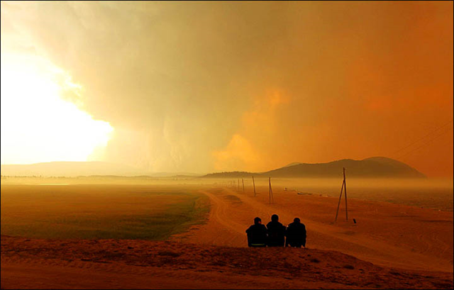 Three people from the town of Gremyachinsk are seated in chairs, watching a huge smoke plume from fires burning around Lake Baikal, on 23 August 2015. Photo: Chono Erdenebayar / The Siberian Times