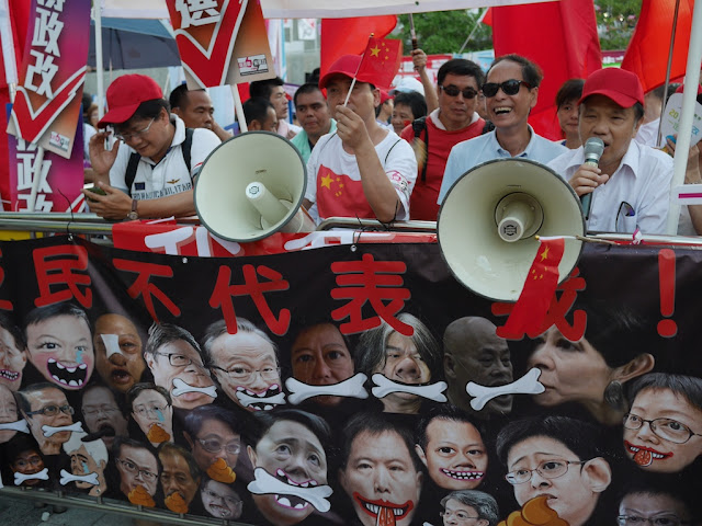 people holding loudspeakers and Chinese flags