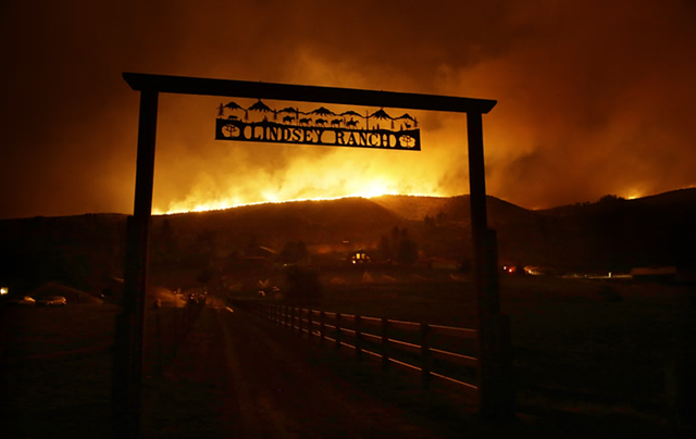 Fire burns into the night on the ridge above the Lindsey Ranch on Twisp River Road, 20 August 2015. Photo: Ted S Warren / AP