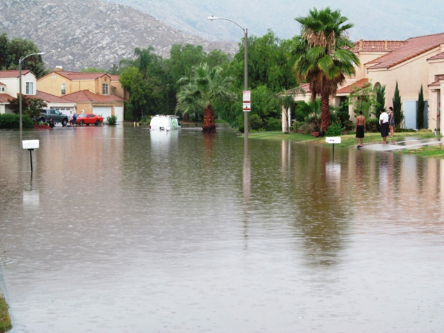 A vehicle proceeds slowly through water covering a road following a downpour in northwest Moreno Valley, Calif, on 19 July 2015. Photo: John Bender / The Press-Enterprise via AP