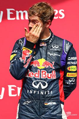 Себастьян Феттель потирает глаз во время гимна на подиуме Гран-при Канады 2014