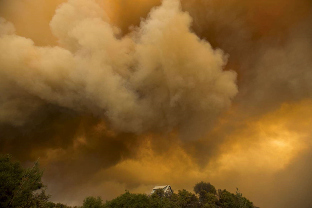 Billowing smoke rises above a residence as the Butte Fire burns in San Andreas, California, on 11 September 2015. Photo: Noah Berger / REUTERS