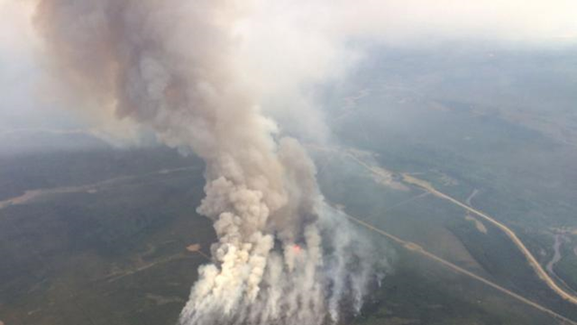 Smoke rises from a wildfire east of Slave Lake, Alberta, on 25 May 2015 in a photo supplied by the Alberta Wildfire Info department. A wildfire raging in northeastern Alberta has shut down around 233,000 barrels per day (bpd) of production at three oil sands projects and is expected to remain out of control for 'some while yet', a provincial government spokesman said on Monday. Over the weekend, Cenovus Energy Inc and Canadian Natural Resources Ltd evacuated staff and halted output at two sites as a precaution against the rapidly spreading forest fire. Photo: Alberta Environment and Sustainable Resource Development (ESRD)