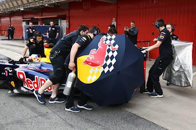 механики Red Bull зарывают болид Себастьяна Феттеля зонтиками после заездов на трассе Каталунья на предсезонных тестах 2012 в Барселоне 4 марта 2012